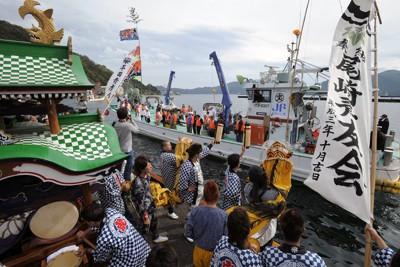 釜石湾を回るみこしを乗せた御召船に向かって伝統の「虎舞」で応える参加者=岩手県釜石市で2011年10月15日午後0時51分、小関勉撮影