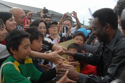 子供たちの歓迎を受ける「サッカーの王様」ブラジルのペレさん(右)=宮城県名取市で2011年10月17日午後1時10分、平川哲也撮影