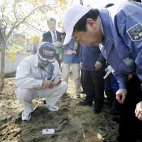 大規模な除染作業が始まり、民家の庭に置かれた線量計を見る野田首相(右・当時)=福島市で2011年10月18日午前11時36分(代表撮影)