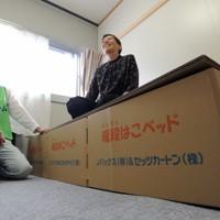 仮設住宅に設置された段ボール製のベット。「思ったよりしっかりした感じで高さも丁度いい」と笑顔を見せる被災者の女性=岩手県陸前高田市で2011年10月18日、小関勉撮影