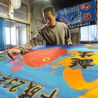 子どもの成長を願う「福来旗」を制作する職人。津波被害に遭った工場を復旧し、人々の「福幸」を願いながら大漁旗などを作っている=宮城県気仙沼市で2011年10月18日、丸山博撮影