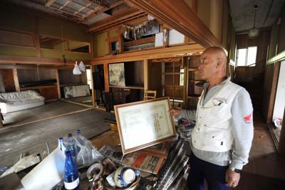 津波被害に遭った自宅を見つめる養殖業の男性。カキやホタテの養殖施設は全滅し、再開のめどは立たない。「海には今も油が浮き、気仙沼の汚水も垂れ流し状態。放射能汚染も心配。行政には、がれき撤去よりも海をきれいにしてほしい」と語気を強めた=宮城県気仙沼市で2011年10月19日午後3時20分、丸山博撮影