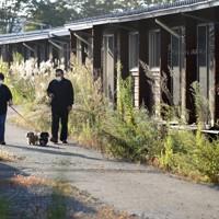 東日本大震災の際に建設された仮設住宅で、愛犬を散歩させる大沼五木さん(右)と妻祐子さん。入居者は少なく、雑草も背を伸ばしていた=福島県本宮市で2020年10月4日、小川昌宏撮影