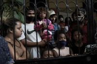 In this Sept. 15, 2020 file photo, squatters peer from behind the iron gate of a house that about 19 families have been occupying for close to a year, before being evicted, amid the new coronavirus pandemic in Rio de Janeiro, Brazil. (AP Photo/Silvia Izquierdo)
