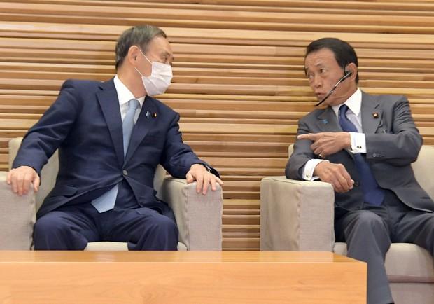 閣議前に言葉を交わす菅義偉首相(左)と麻生太郎財務相兼金融担当相=首相官邸で2020年9月29日午前10時、竹内幹撮影