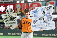 Tomoyuki Sugano, a pitcher for the Yomiuri Giants, poses for a commemorative photo at Tokyo Dome on Oct. 6, 2020, to celebrate a career record of 100 wins and setting a new pro baseball record of achieving 13 consecutive wins since the first game of the season. (Mainichi/Toshiki Miyama)