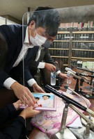 Takuya Matsunaga, left, is seen storing away a portrait of his wife Mana and daughter Riko after a press conference at the judicial press club in Tokyo's Kasumigaseki district on Oct. 8, 2020. (Mainichi/Masahiro Ogawa)