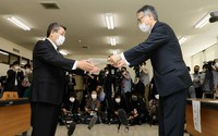 Masayuki Takahashi, mayor of the village of Kamoenai, left, is seen accepting a written request from an economy ministry official, right, regarding preliminary research for selecting the final disposal site of nuclear waste in Kamoenai, Hokkaido, on Oct. 9, 2020. (Mainichi/Taichi Kaizuka)