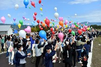 People are seen releasing balloons on Oct. 11, 2020, at a levee of the Chikuma River, in the Hoyasu district of the central Japan city of Nagano, which had been repaired after its collapse caused by Typhoon Hagibis in 2019. (Mainichi/Daiki Takikawa)