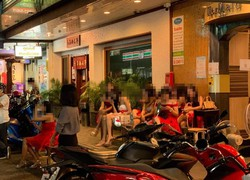 タイのタニヤ通りで、店の前に座り客を待つ性風俗店の従業員ら=10月6日