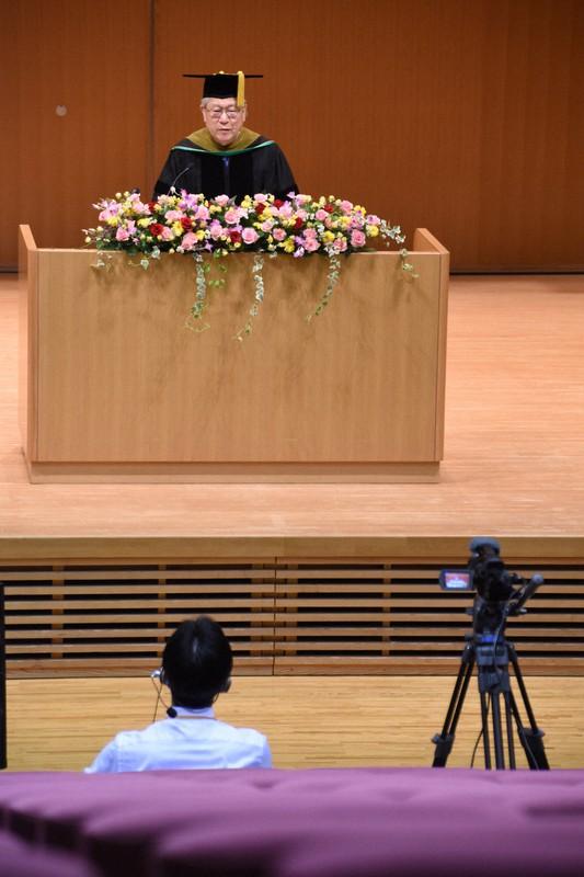 空席の多目的ホールでカメラを前に式辞を述べる国際教養大の鈴木典比古学長(奥)。同大学は学生全員を留学させる方針だったが・・・