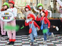 Children dressed up in Mario costumes dance during a press event held ahead of the opening of