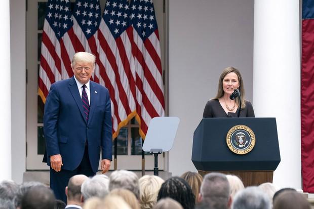 トランプ大統領は9月26日、故ギンズバーグ連邦最高裁判事の後任にバレット連邦高裁判事(右)の指名をホワイトハウスで発表した (Bloomberg)