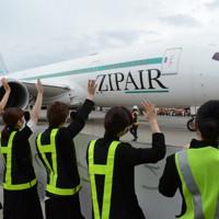 手を振って出発する機体を見送るZIPAIRの社員=成田空港で2020年10月16日午前9時14分、中村宰和撮影