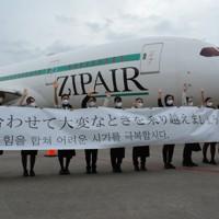 初便の機体の前で横断幕を持って手を振るZIPAIRの社員=成田空港で2020年10月16日午前9時12分、中村宰和撮影