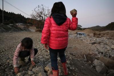 台風19号の豪雨で阿武隈川の支流、五福谷川が氾濫し、土石流がなだれこんだ佐久間新平さん宅前で遊ぶ子供たち。佐久間さんは「家の前も川のようになって、家や田畑が土砂や岩に埋まって、車も押し流されていた」と振り返った=宮城県丸森町で2019年11月8日、和田大典撮影