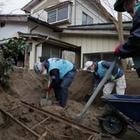 豪雨で住宅になだれ込んだ土砂などを取り除くボランティアの人たち=宮城県丸森町で2020年1月18日、和田大典撮影