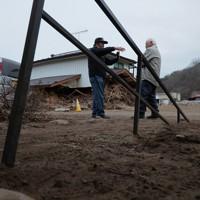 道路から約1・5㍍高い土台にある集会所には土砂がたまり、階段の手すりもほとんど埋まっていた=宮城県丸森町で2020年1月18日、和田大典撮影