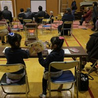 生活再建について考えるため町内の住民たちが勉強会をする会場の後方で、宿題をする子供たち=宮城県丸森町で2020年2月4日、和田大典撮影