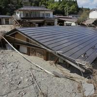 台風19号の豪雨で五福谷川が氾濫し、屋根の上まで土砂に埋まったままの民家=宮城県丸森町で2020年4月9日、和田大典撮影