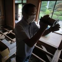 「忘れないように撮っておきたい」。解体を前に、浸水被害の爪痕が残る築28年の自宅をビデオカメラで撮影する佐久間新平さん。息子夫婦や孫と一緒に暮らした思い出の場所は10月5日に解体工事が始まった=宮城県丸森町で2020年9月19日、和田大典撮影