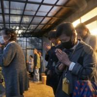 台風19号上陸から1年を迎え、集会所で、災害で亡くなった方々を悼み黙とうする住民たち=宮城県丸森町で2020年10月11日、和田大典撮影