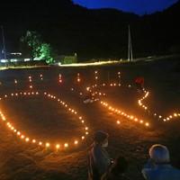 台風19号上陸から1年となり、集荷所前で、「10・12」の形に並べられた竹灯籠(とうろう)=宮城県丸森町で2020年10月12日、和田大典撮影