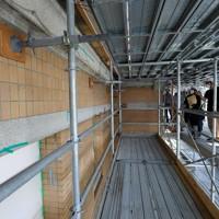 工事用足場から外壁の状態の説明を受ける見学会参加者ら=大阪府田尻町で2020年10月3日、大西達也撮影