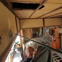 台風19号で夏井川などが氾濫し、深夜に水がおしよせ、屋根裏へ避難するため頭突きで開けた天井の穴が残る自宅で洗濯物を干す根本徳一さん=福島県いわき市で2019年11月13日、和田大典撮影
