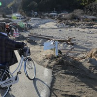 台風19号の豪雨で、阿武隈川の支流、五福谷川が氾濫し土砂や岩が流れこんだ集落を見つめる住民=宮城県丸森町で2019年12月25日、和田大典撮影