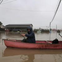 台風19号の豪雨で氾濫した吉田川の水で1週間たっても浸水したままの自宅へ船で向かう住民たち=宮城県大崎市で2019年10月19日、和田大典撮影