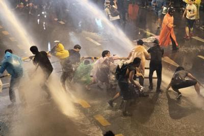 タイの首都バンコクで治安部隊からの放水を受けるデモ隊=2020年10月16日、AP