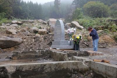 上陸から1年となる台風19号で亡くなった住民の自宅跡に置かれた鎮魂の石碑の前で、通勤前に手をあわせる親族=宮城県丸森町で2020年10月12日午前7時56分、和田大典撮影