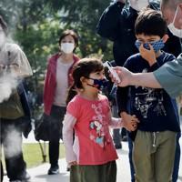 検温チェックを受け、「ウイルスバスターウォーター」が噴霧される門を通過する子どもたち=東京都台東区で2020年10月18日、滝川大貴撮影