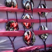 御用車と神輿を固定する作業に汗を流す担ぎ手が映り込んだ神輿の装飾品=東京都台東区で2020年10月18日、滝川大貴撮影