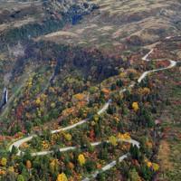 紅葉が見ごろを迎えた「立山黒部アルペンルート」。立山連峰の山頂付近はうっすらと雪化粧していた=富山県立山町で2020年10月18日、本社ヘリから大西達也撮影