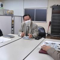 福島県産食品などへの風評払拭を目指す草の根活動について打ち合わせる簡憲幸さん(左)=福島市内で14日