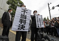 Lawyers of plaintiffs are seen holding signs expressing opposition to a Supreme Court ruling that declared that the inequal treatment of regular and nonregular employees is reasonable, following a lawsuit filed by a part-time employee at Osaka Medical and Pharmaceutical University, in front of Japan's Supreme Court in Tokyo's Chiyoda Ward on Oct. 13, 2020. (Mainichi/Kota Yoshida)