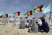 In this Sept 14, 2020 file photo, families gather at the graves of their relatives, adorned with their pictures, on the outskirts of Kabul, Afghanistan. (AP Photo/Rahmat Gul)