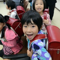 贈られたランドセルを背負い笑顔を見せる子どもたち=福島市の飯舘村役場飯野出張所で2012年10月28日、宮間俊樹撮影