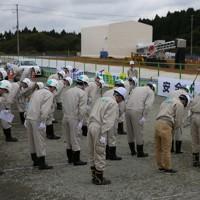 中間貯蔵施設の土壌貯蔵施設を前に一礼する環境省職員たち=福島県大熊町で2017年10月28日午後1時37分、小出洋平撮影