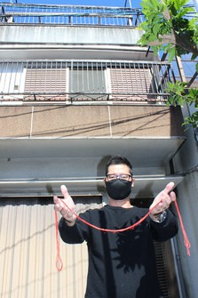 Daisaku Yoshimura stands in front of the home that is waiting to be bartered, with some red thread that started it all in his hands. (Courtesy of Daisaku Yoshimura)