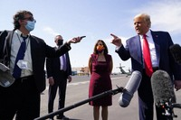 President Donald Trump talks to reporters at Phoenix Sky Harbor International Airport, on Oct. 19, 2020, in Phoenix. Second from right is Sen. Martha McSally, R-Ariz. (AP Photo/Alex Brandon)