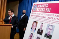 A poster showing six wanted Russian military intelligence officers is displayed as Assistant Attorney General for the National Security Division John Demers, left, takes the podium to speak at a news conference at the Department of Justice, on Oct. 19, 2020, in Washington.  (AP Photo/Andrew Harnik)