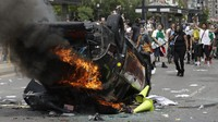 In this May 30, 2020 file photo, protesters demonstrate as a Salt Lake City police vehicle burns, in Salt Lake City. (AP Photo/Rick Bowmer)