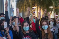 Pro-democracy activists flash three-fingered salutes while listening to the national anthem outside Siam Paragon, one of the largest shopping malls, in Bangkok, Thailand, on Oct. 20, 2020. (AP Photo/Sakchai Lalit)