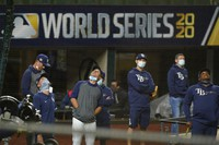 Tampa Bay Rays manager Kevin Cash, center with face mask down, watchers over a practice at Globe Life Field as the team prepares for the baseball World Series against the Los Angeles Dodgers, in Arlington, Texas, on Oct. 14, 2020. (AP Photo/Eric Gay)