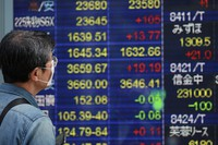 A man looks at an electronic stock board of a securities firm in Tokyo on Oct. 21, 2020. (AP Photo/Koji Sasahara)
