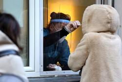 ベルリンで窓越しに検査を行う医療従事者(Bloomberg)