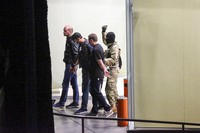 A gunman with a weapon in hand, escorts three police officers, who surrendered themselves as hostages, out of the bank building in the town of Zugdidi in western Georgia, on Oct. 21, 2020. (AP Photo/Zurab Tsertsvadze)